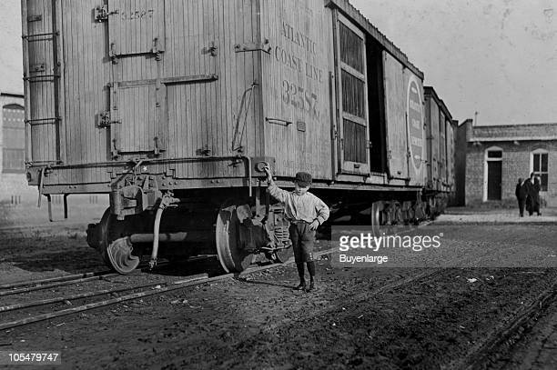 A young boy stands beside a boxcar at Maple Mills in Dillon SC 1908 Eight year old Johnnie said that he 'ain't got no last name' and was beginning to...