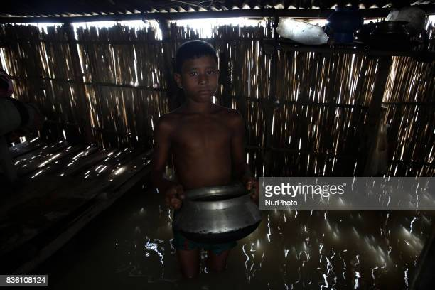 Young boy stands highdeep in flood water after he collecting water from a tube wale in Islampur Jamalpur Bangladesh on 19 August 2017
