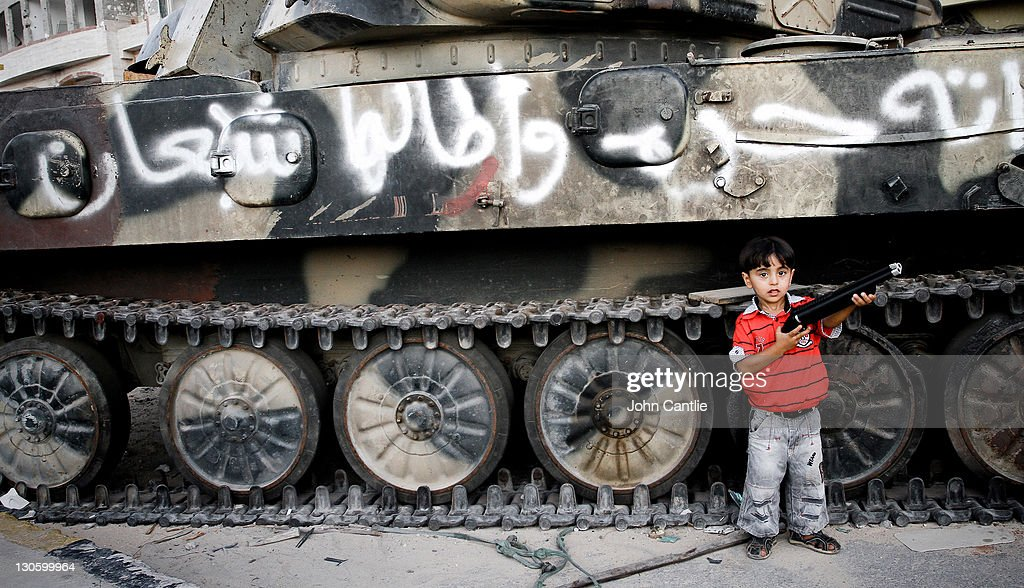 A young boy stands in front of a Gaddafi loyalist tank smashed by NTC forces in Tripoli Street on September 08, 2011 in Misrata, Libya. NTC forces are continuing to advance on Colonel Muammar Gaddafi's home town of Sirte. .