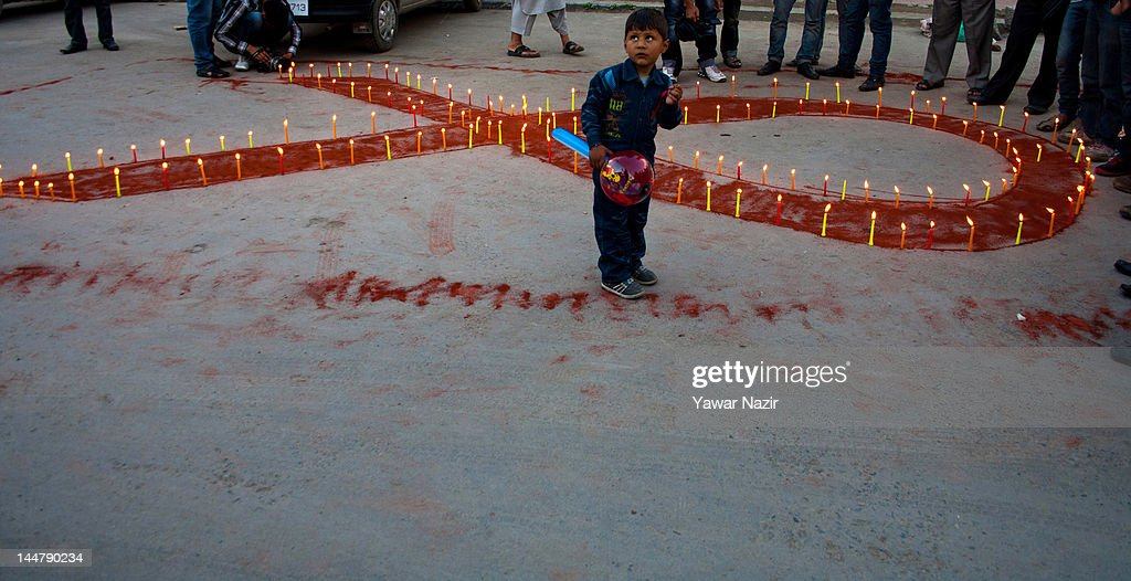 A young boy stands in front of a symbolic red ribbon during a candlelight vigil on May 19, 2012 in Srinagar, the summer capital of Indian Administered Kashmir, India. A candle light vigil was organized to commemorate the International AIDS Candlelight Memorial Day for HIV awareness.