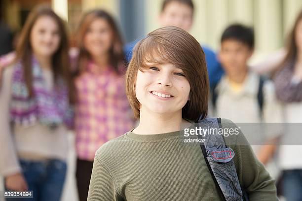 Muchacho joven está en frente de otro amigo estudiantes