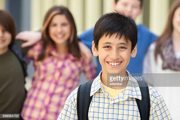 Giovane ragazzo sta di fronte a un altro amico studenti