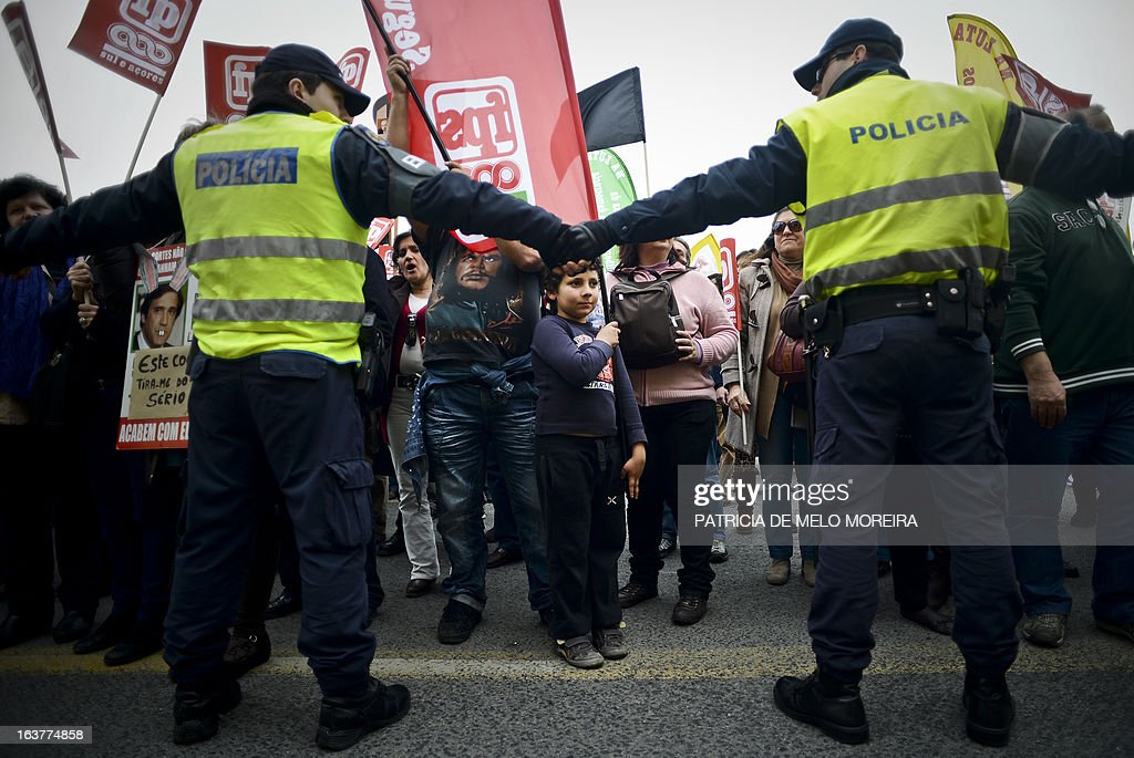 A young boy stands in front of policemen during a demonstration called by the unions Common Front, CGTP (General Confederation of the Portuguese Workers) and STAL (National Union of the Local and Regional Public Workers) against the austerity measures of the Portuguese government in Lisbon on March 15, 2013. Today the Finance Minister, Vitor Gaspar, said that the GDP (Gross Domestic Product) will drop 2.3%, that unemployment might reach 19% and the adjustment effort will have to continue for decades.'