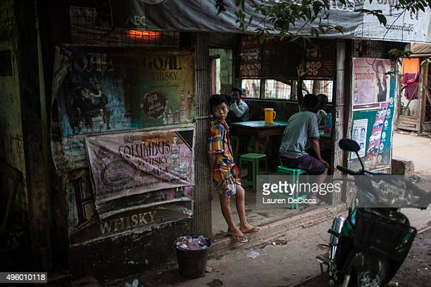 A young boy stands in the doorway of an old teashop on November 6 2015 in Kawhmu near Yangon Myanmar an impoverished ricegrowing area with an...