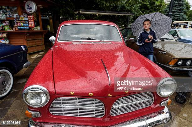 A young boy stands next to a vintage Volvo car displayed displayed during the 12th Old Timer Fest on July 17 2017 in the historic city of Prizren in...