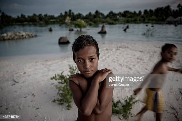 A young boy stands on a narrow strip of land that luckily didn't flood and prevented his home from being drowned in the sea with the village Eita The...