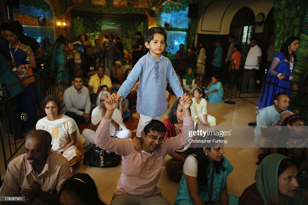 A young boy stands on his fathers shoulders as devotees pray inside the temple at the Janmashtami Hindu Festival at Bhaktivedanta Manor on August 28, 2013 in Watford, England. Up to 72,000 were expected to take part in the Hindu festival of 'Janmashtami', which falls on August 28 this year, and marks the birth of the Hindu god Lord Krishna. The festival is believed to be the largest Hindu festival gathering outside of India. Bhaktivedanta Manor is also celebrating it's 40th year since the manor house was donated to the Society of Krishna Consciousness by George Harrison in 1973.