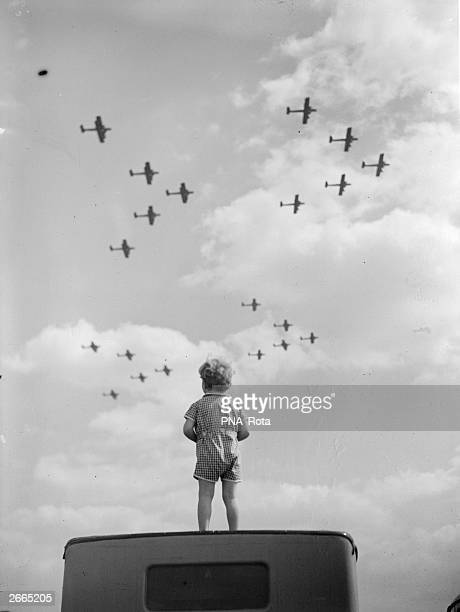 A young boy stands on the roof of a car to watch RAF aeroplanes flying in formation over Duxford in south east England