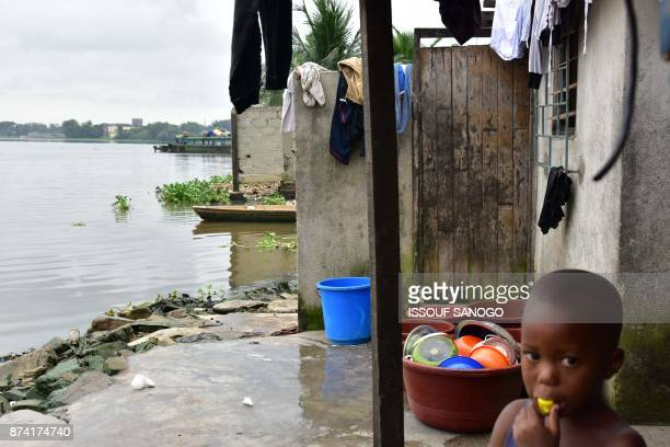 A young boy stands outside a toilet in an impoverished neighbourhood near a lagoon in Abidjan on November 14 2017 / AFP PHOTO / ISSOUF SANOGO