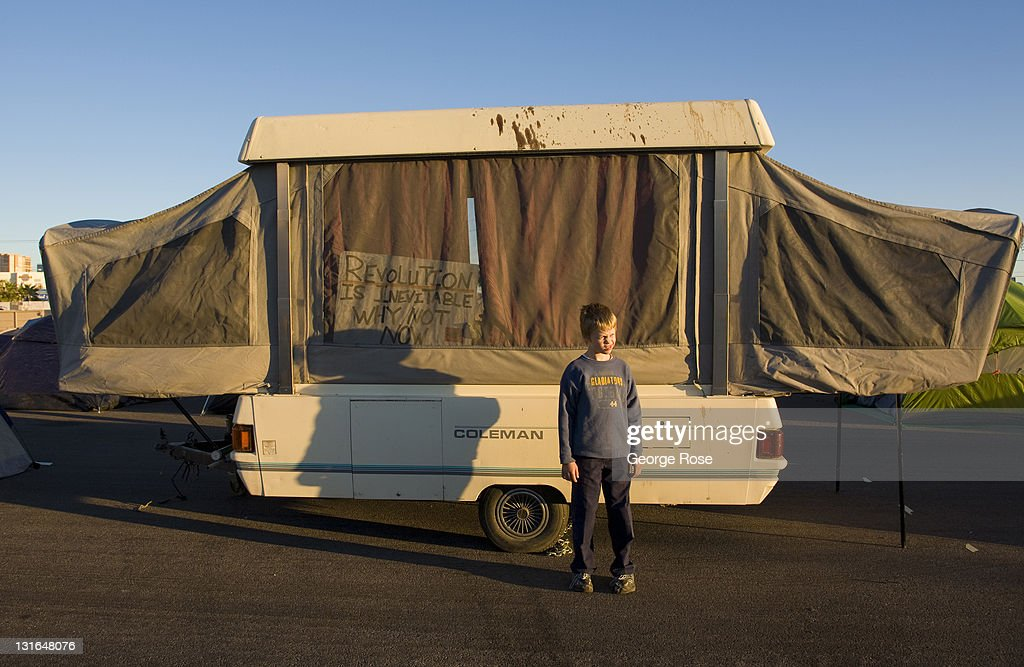 A young boy stands outside his family's pop-up trailer at the Occupy Las Vegas camp on October 23, 2011 in Las Vegas, Nevada. Located a vacant lot across from the University of Nevada near McCarran International Airport, the turnout by protesters appeared on this day to be low.
