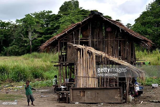 A young boy stands outside his house near the town of Malalaua in the jungle of Papua New Guinea on September 3 2014 AFP PHOTO / ARIS MESSINIS