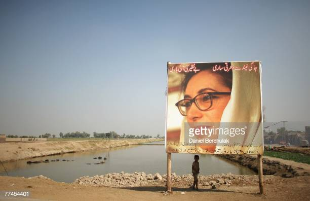A young boy stands underneath a bilboard of Benazir Bhutto in her home town of Larkana on October 23 2007 in Larkana Pakistan Bhutto is expected to...
