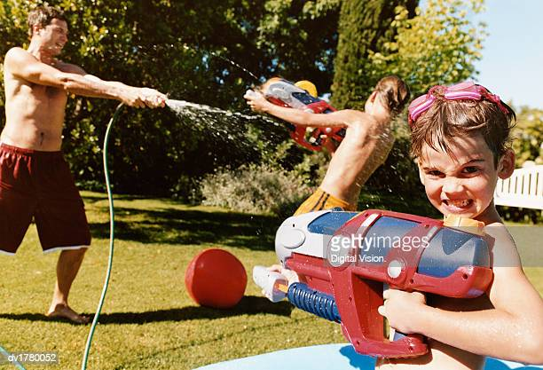 Young Boy Stands With a Water Pistol as His Father Sprays Water From a Hose
