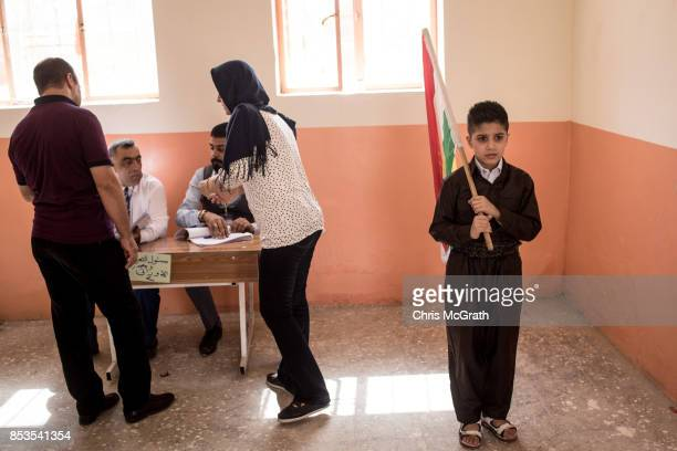 A young boy stands with the Kurdish flag as he waits for his parents to cast their referendum vote at a voting station on September 25 2017 in Kirkuk...