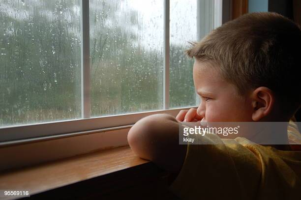 Young boy staring out a window as it rains