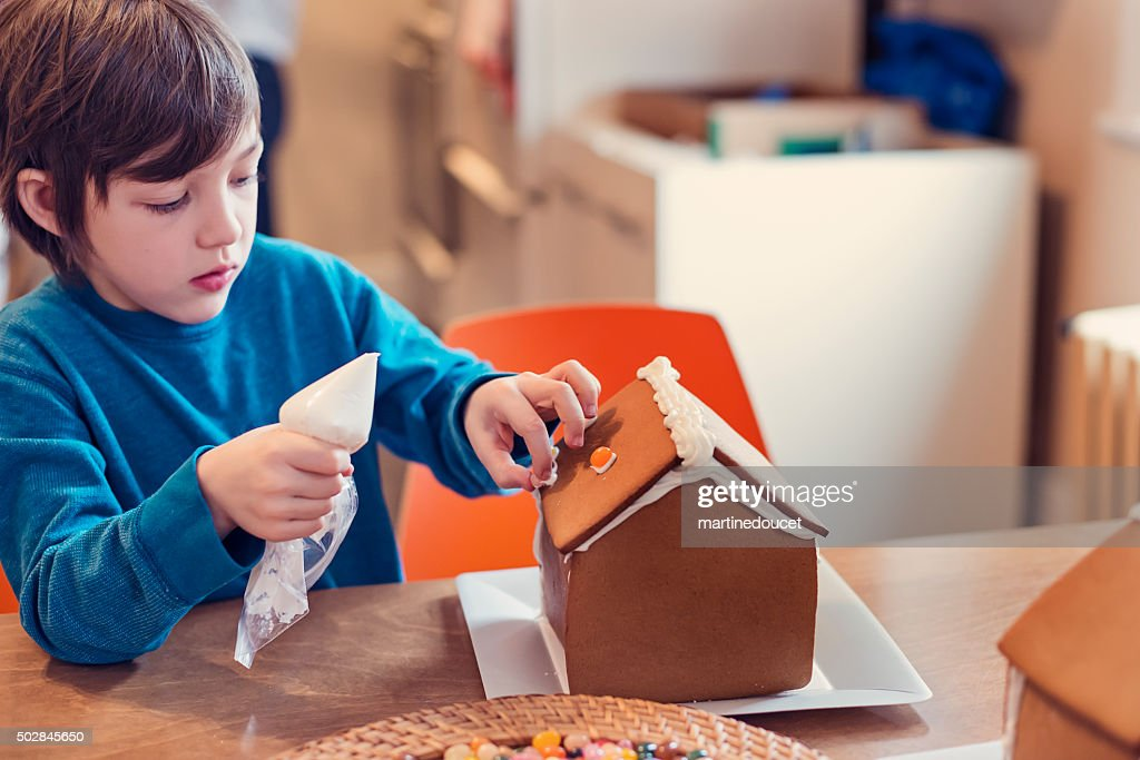 Young boy starting to decorate gingerbread house with candy.