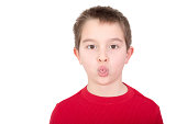 Playful young boy sticking out his tongue in a mischievous gesture or in an act of rudeness isolated on white