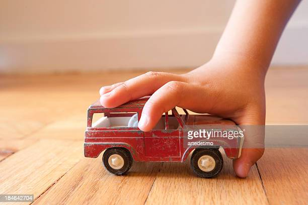 Young boy stopping a toy SUV in its tracks