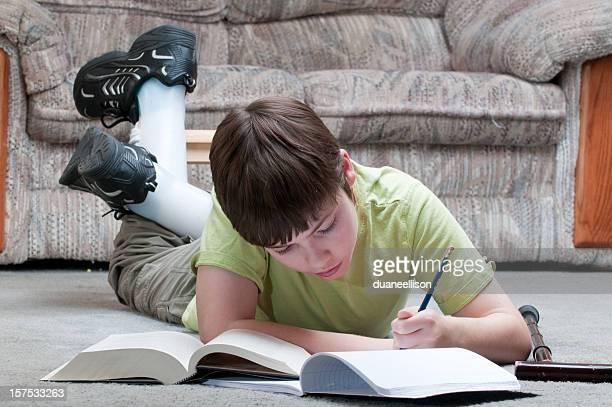 Young boy studies homework on floor