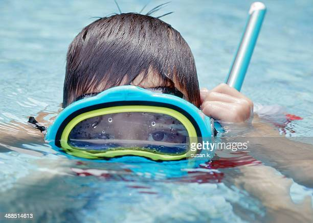 Young boy submerging from pool with snorkel