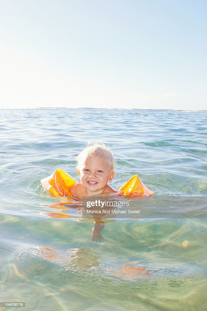 Young boy swimming in the ocean with water wings : Stock Photo