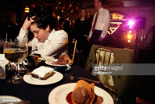 A young boy takes a break from the festivities near plates of desserts at a bat mitzvah celebration for 13yearold Ali Green The reception takes place...