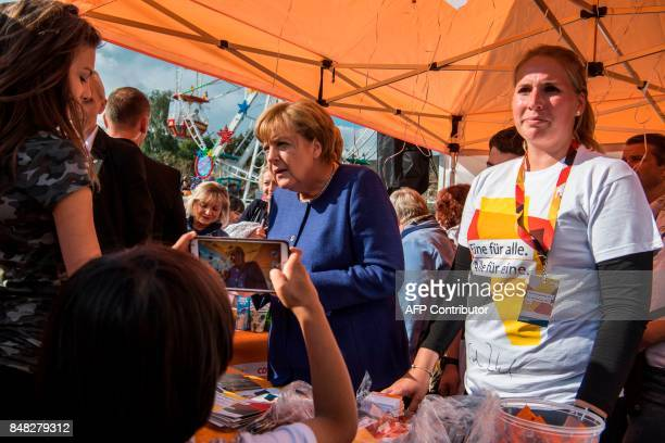 A young boy takes a picture of German Chancellor Angela Merkel as she signs autographs at a neighbourhood fair organised by the local branch of the...