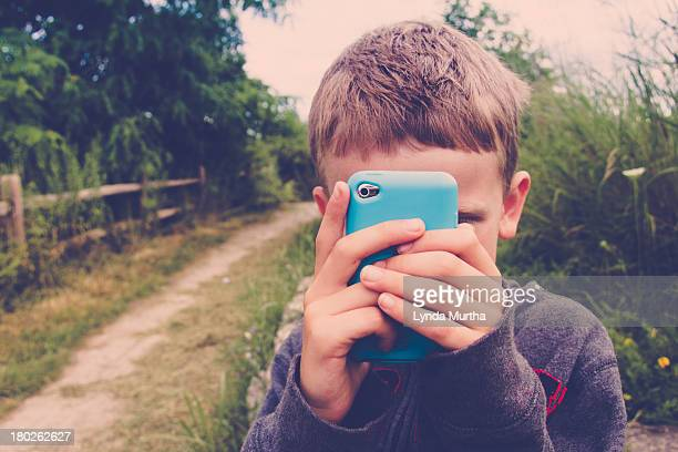 Young boy taking photo with mobile device