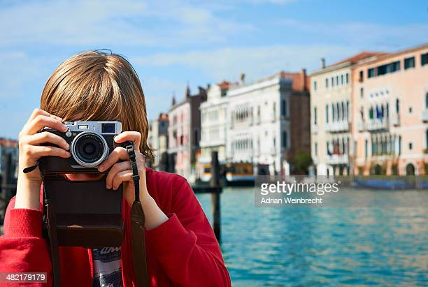Young boy taking photographs, Venice, Italy