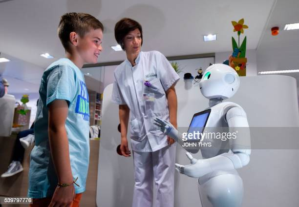 A young boy talks with the robot Pepper next to a nurse during a press conference on June 13 2016 at the CHR Citadel hospital centers of Liege the...