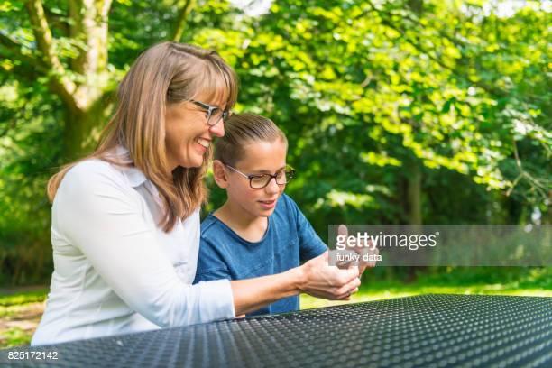 Young boy teaching mother fidget spinner