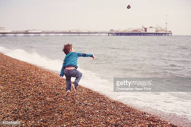Young boy throwing a stone on a beach