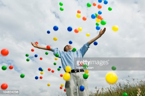 Young boy throwing colored balls