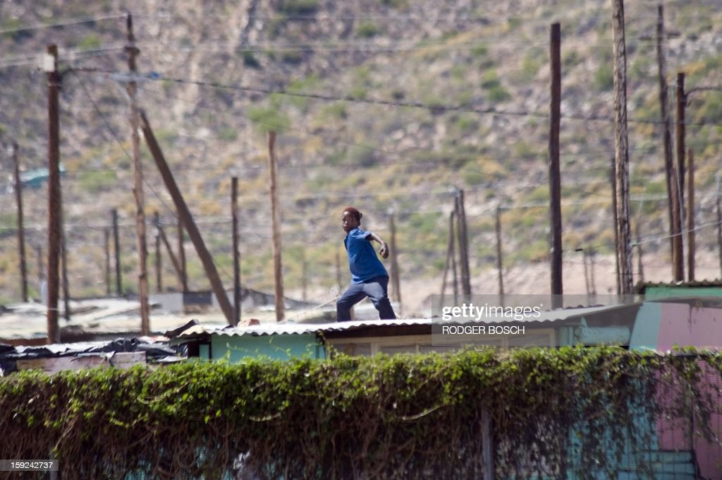 A young boy throws rocks as Members of the South African Police Services clash with striking farmworkers(not visible), on January 10, 2013 in De Doorns, a small farming town about 140Km North of Cape Town, South Africa. The farm workers have said that they they will not return to work on the fruit growing region's farms until they receive a daily wage of at least R150($17) per day, which is about double what they currently earn. AFP PHOTO / RODGER BOSCH