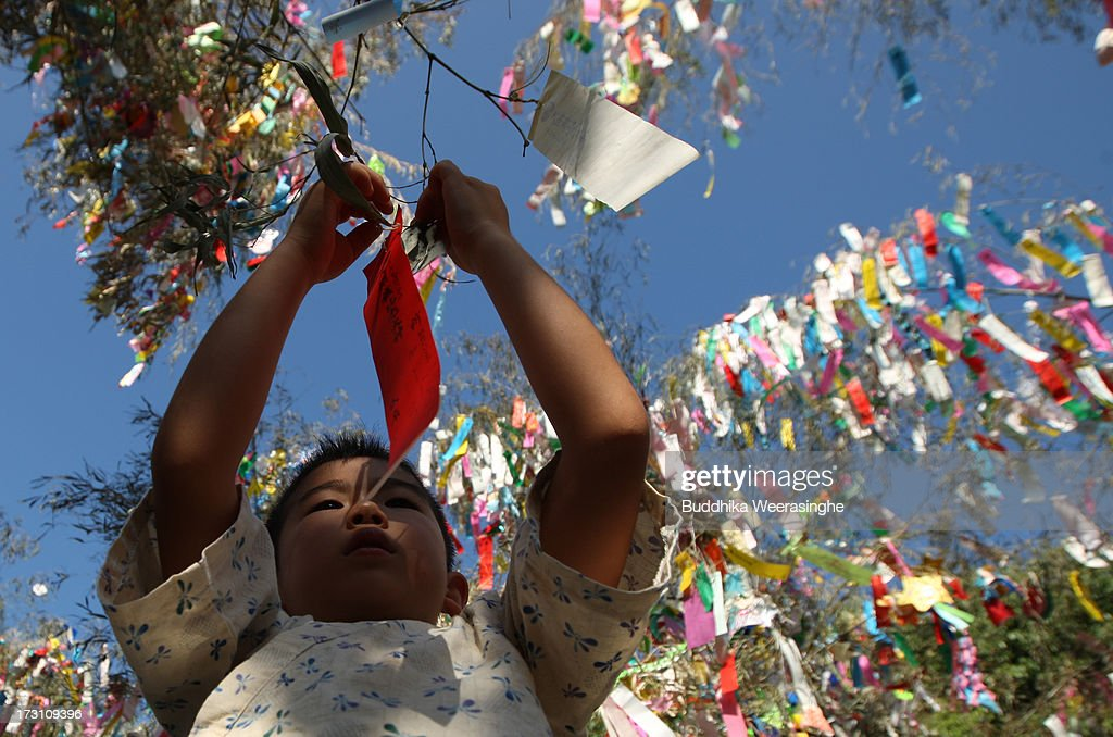 A young boy ties a paper strip with his wish on it onto a bamboo decoration during the Tanabata festival at the Hatamono shrine on July 7, 2013 in Osaka, Japan. Tanabata is a Japanese star festival in which people wear traditional ''yukata'' robes and write their wishes on strips of paper to hang on bamboo trees.