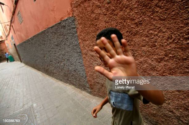 Young boy trying to avoid photograph of himself.
