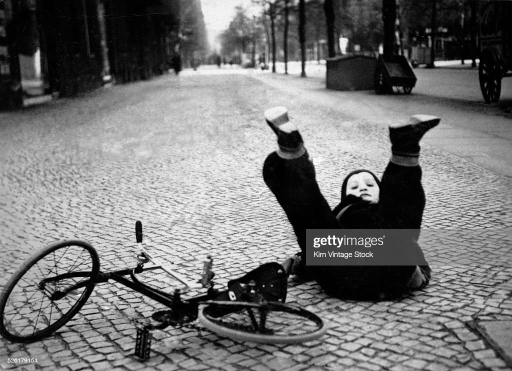 A young boy tumbles off his bike on a German cobblestone street in 1934.