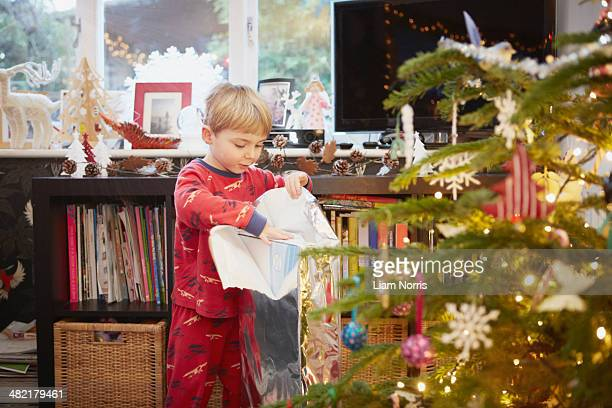 Young boy unwrapping gift at christmas