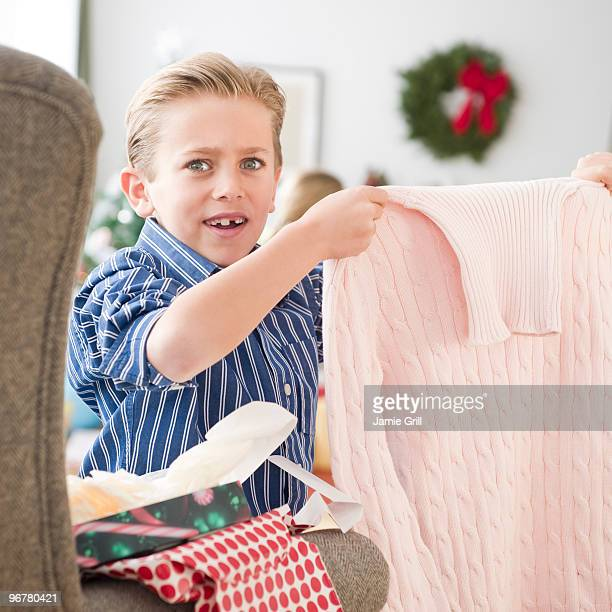 Young boy unwrapping gift on Christmas, unhappy