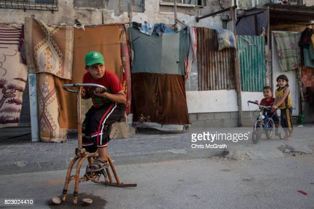 A young boy uses a damaged exercise bike outside his home in the Beit Lahia neighborhood on July 24 2017 in Gaza City Gaza For the past ten years...