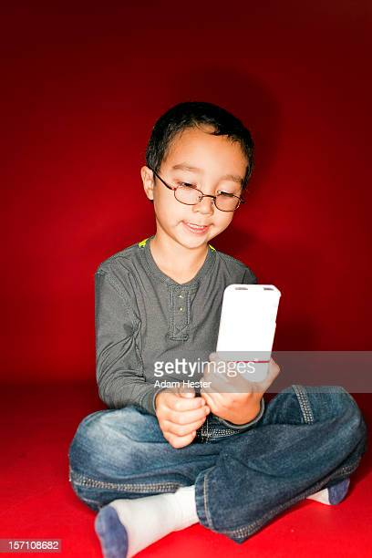 A young boy using a cellular device inside.