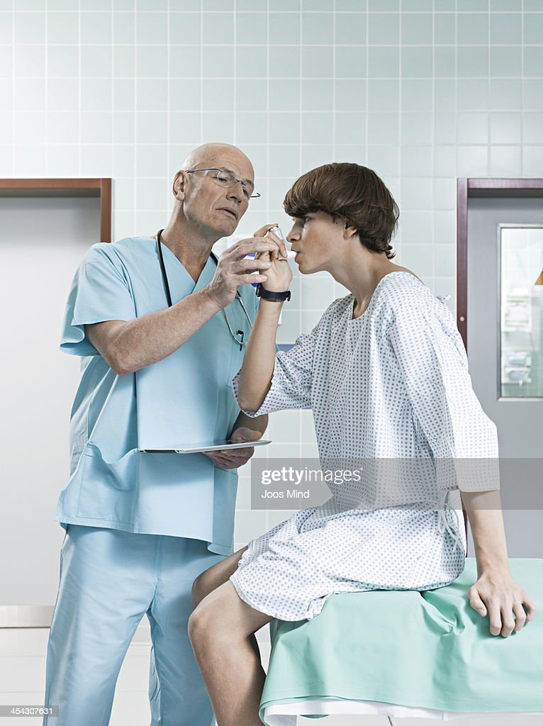 young boy using asthma inhaler, doctor helping : Stock Photo