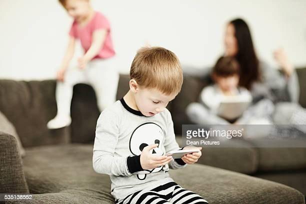 Young boy using cell phone in living room with family