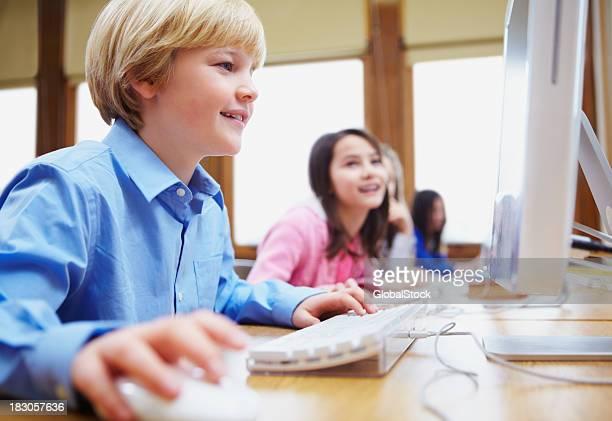 Junge mit computer mit Kindern im Hintergrund