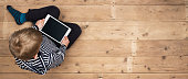 Top view header image of young boy using digital tablet. Web banner with copy space