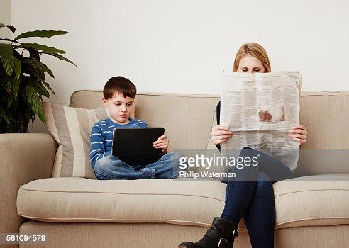 Young boy using digital tablet, mother reading newspaper