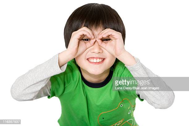 Young boy using hands to make glasses