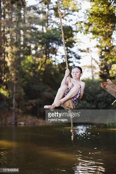 Jeune garçon à l'aide de la corde swing sur le lac