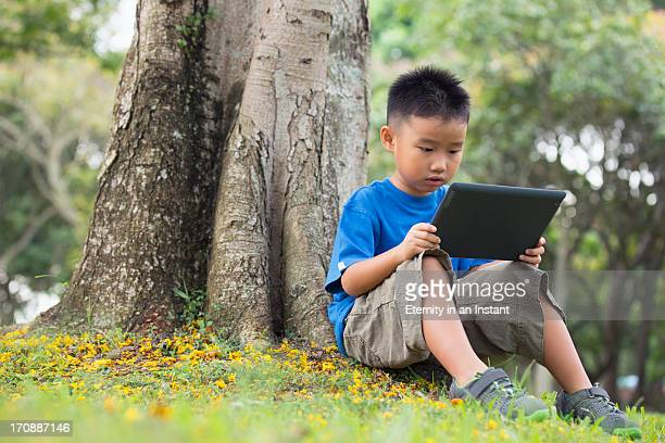 Young boy using tablet device by tree