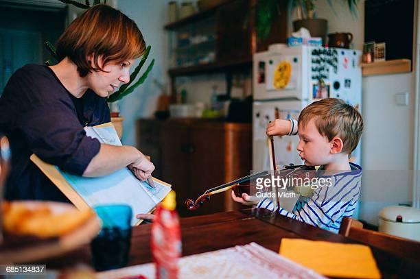Young boy using violin.